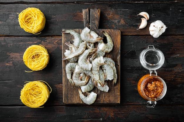 Лапша с набором ингредиентов из морепродуктов, на старом темном деревянном столе, плоская планировка, вид сверху
