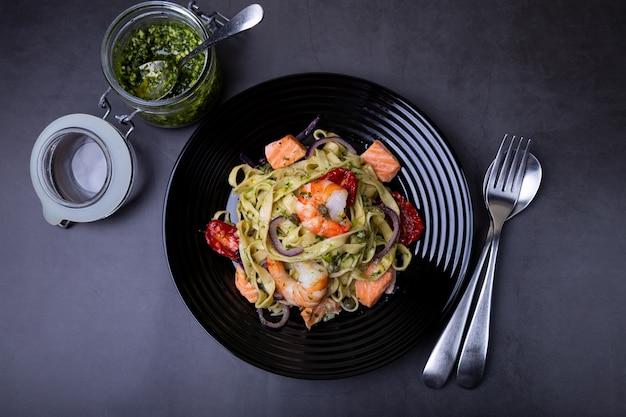 해산물, 선드라이 토마토, 케이퍼, 적양파를 곁들인 국수. 새우, 연어(송어), 페스토 소스를 곁들인 홈메이드 파스타. 검은 배경, 검은 접시. 확대.