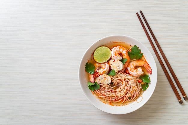 白いボウルにスパイシーなスープとエビが入った麺(トムヤムクン)。アジアンフードスタイル