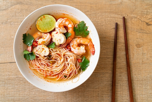 Noodles with spicy soup and shrimps in white bowl (tom yum kung)  - asian food style