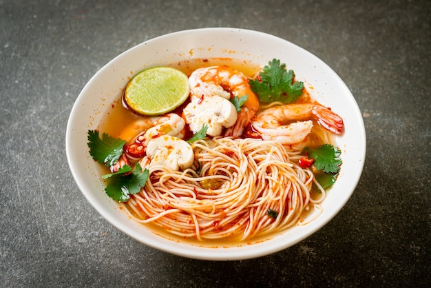 Noodles with spicy soup and shrimps in white bowl (tom yum kung)
