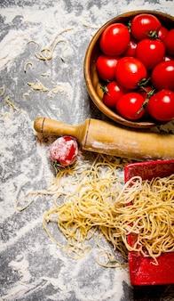 トマトをカップに入れて麺棒でつなぐ麺。小麦粉の入った石のテーブルの上。上面図