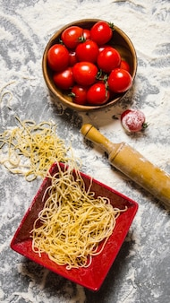 Noodles with tomatoes and a rolling pin. on the stone table with flour. top view