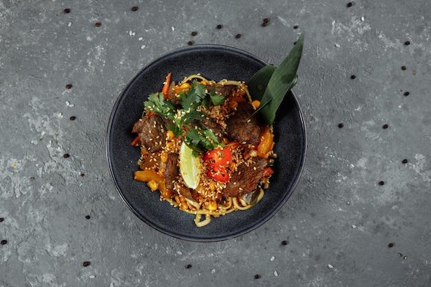 회색 테이블에 송아지 고기와 야채 국수