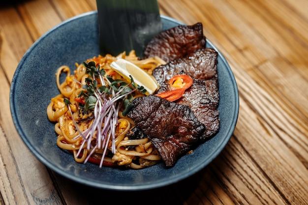 회색 테이블에 송아지 고기와 야채 국수.