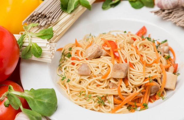 Лапша с овощами и гарниром на белой тарелке