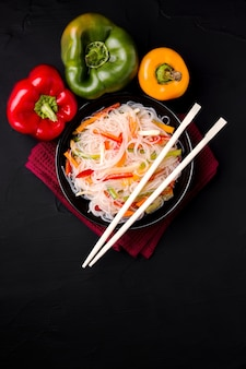 Noodles with vegetables on a black background