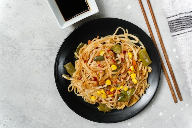 Noodles with vegetables in a black plate with soy sauce top view.