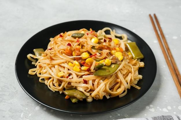 Лапша с овощами в черной тарелке с видом сверху соевого соуса.