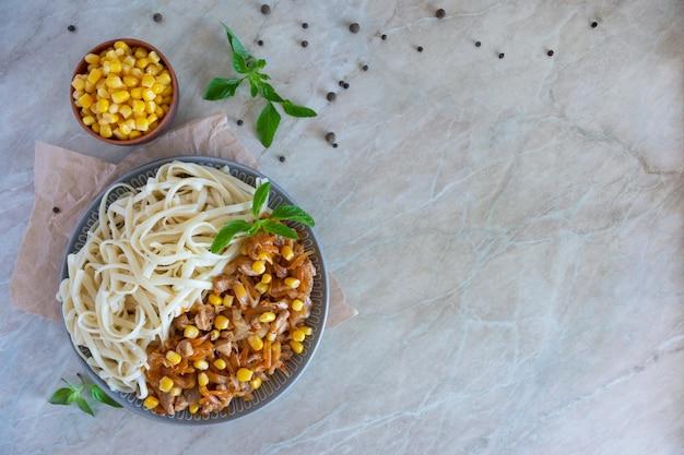 大きな皿に野菜の入った麺。ボウルにトウモロコシ粒。テーブルの上の伝統的な健康的な東洋料理。