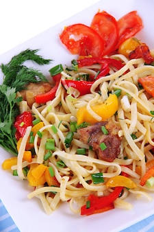 Noodles with vegetables on plate close-up