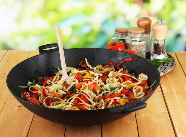 Noodles with vegetables on wok on nature