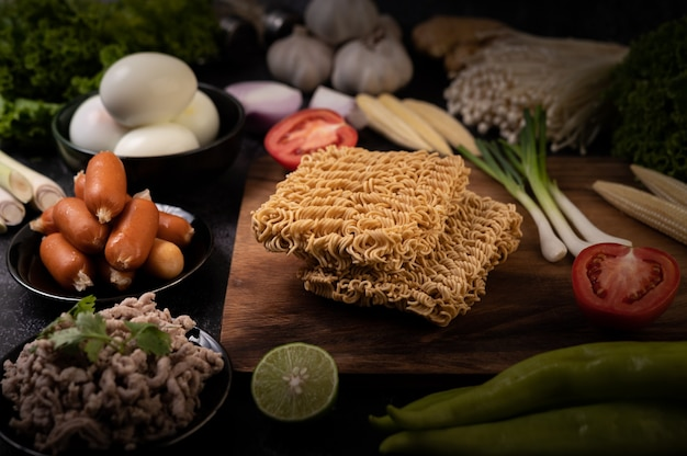 Noodles on a wooden cutting board with tomato, lime, spring onion, chili and baby corn Free Photo