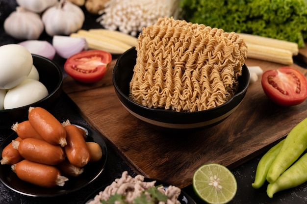 Noodles on a wooden cutting board with tomato, lime, spring onion, chili and baby corn