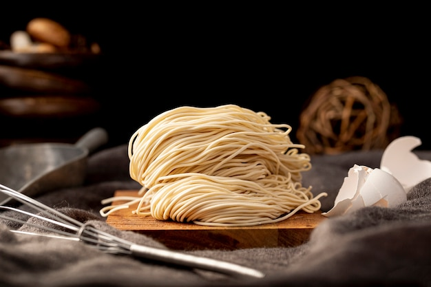 Noodles on a wooden plate on a black background