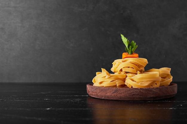 Tagliatelle su un piatto di legno con verdure