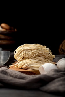 Noodles on a wooden support on a black background