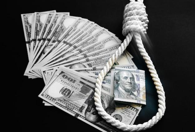 縄とお金は黒い背景の上に横たわっています。自殺の概念。巨額のローンのためにぶら下がっています。借金を伴ううつ病。