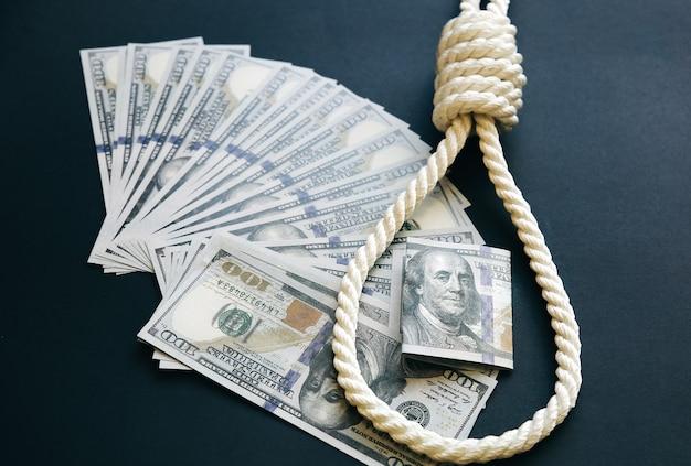 올가미와 돈이 검은 배경에 누워 있습니다. 자살 개념입니다. 거액의 대출로 인해 중단되었습니다. 부채로 인한 우울증.