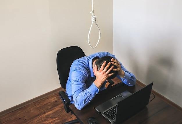 올가미는 회사원 위에 있습니다. 자살 개념입니다. 업무 스트레스로 인해 매달려 있습니다. 소진의 우울증. 끔찍한 생활 상황. 책상에 노트북 근처 남자입니다.