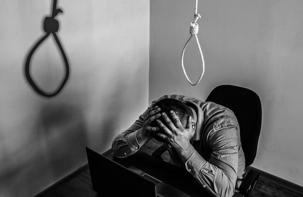 縄はサラリーマンの上にいます。自殺の概念。仕事のストレスのためにぶら下がっています。燃え尽き症候群のうつ病。ひどい生活状況。机の上のラップトップの近くの男。