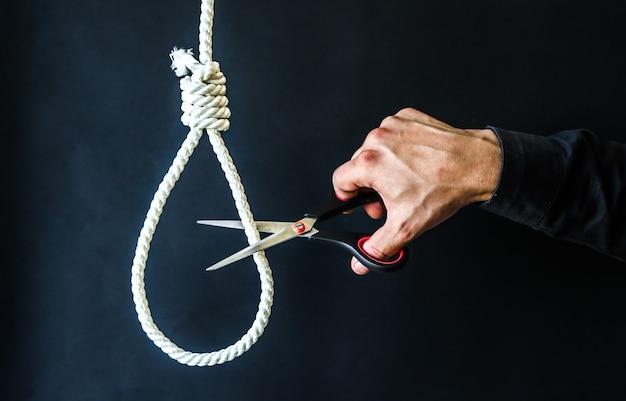 Петля на шее. мужчина держит в руках ножницы. концепция самоубийства. зависание из-за стресса на работе. депрессия или выгорание. ужасная жизненная ситуация.