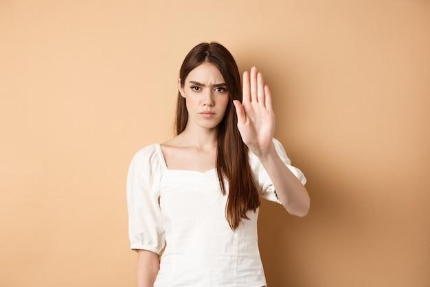 거기에서 멈추지 마십시오. 진지하고 자신감있는 여자는 베이지 색 배경에 서서 무언가를 금지하고 찌푸리고 거절하고 동의하지 않고 나쁜 제안을 거부하기 위해 손을 뻗습니다.