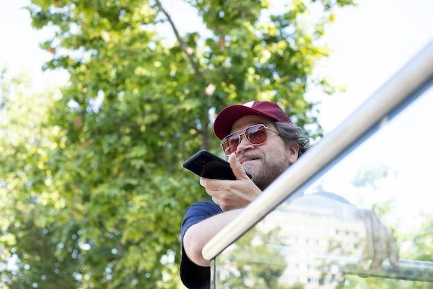 Скандинавский мужчина в солнечных очках случайно разговаривает по мобильному телефону на открытом воздухе