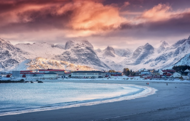 Nordic sandy beach with blue sea in winter at sunset in lofoten islands, norway.