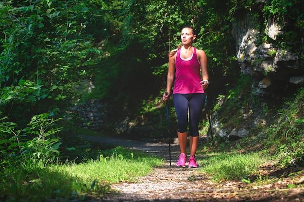 노르딕 워킹. 숲에서 하이킹에 젊은 여자