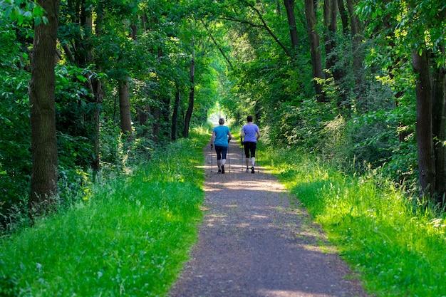 ノルディックウォーキング-公園で運動するアクティブな人々。