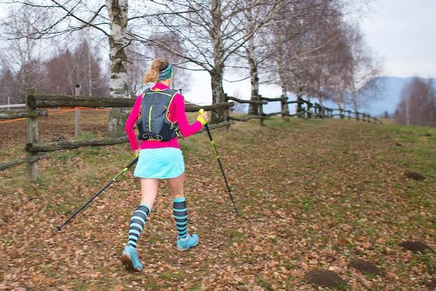 산에서 가을 흔적에 노르딕 워킹 소녀