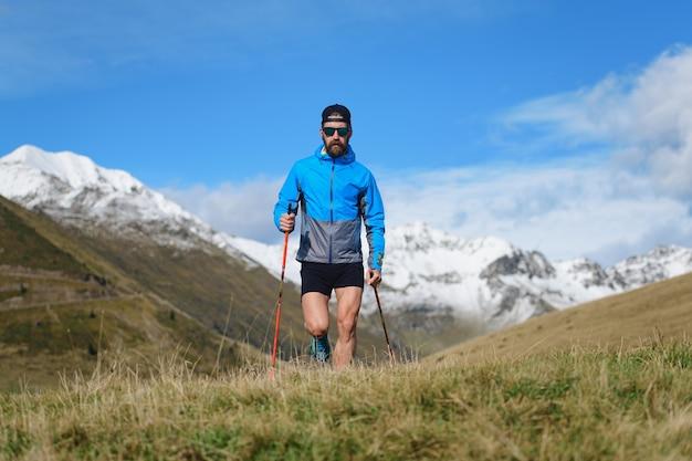 젊은 남자 산에서 노르딕 워킹