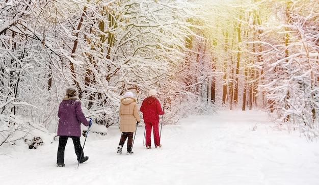 雪に覆われたウィンターパークを歩くノルディックウォーキング。