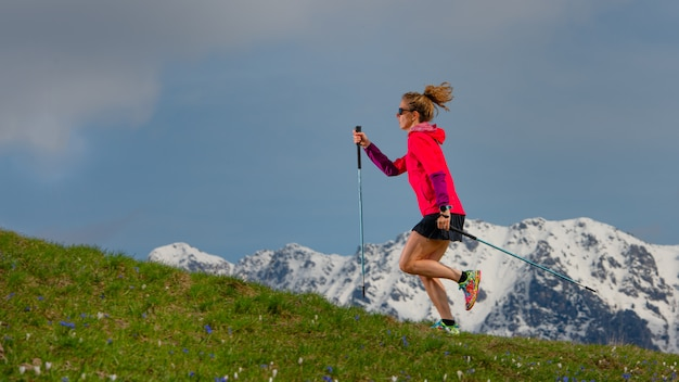 Nordic walking and trail running a girl with sticks on spring mountain bream with snowy background