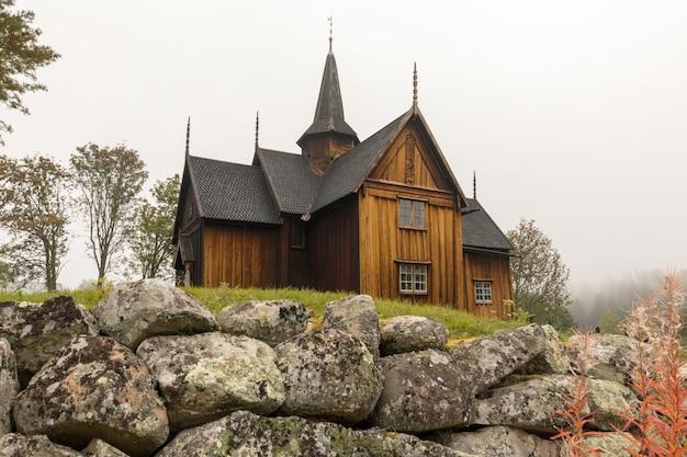 노르웨이 노레 앞에 돌 울타리가 있는 노어 통나무 교회