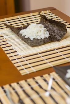 Nori seaweed sheet with rice above ready to make japanese sushi rolls