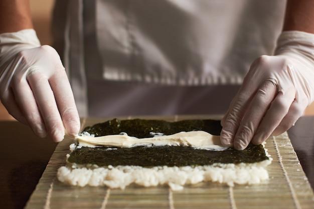 Nori, white rice and chees on bamboo mat
