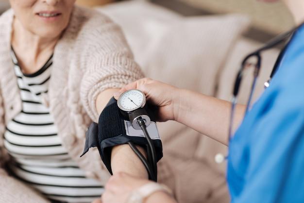 정상적인 결과. 집에서 노인 여성을 방문하는 동안 검사를 수행하면서 특수 의료 장비를 사용하는 숙련 된 신중한 의료인