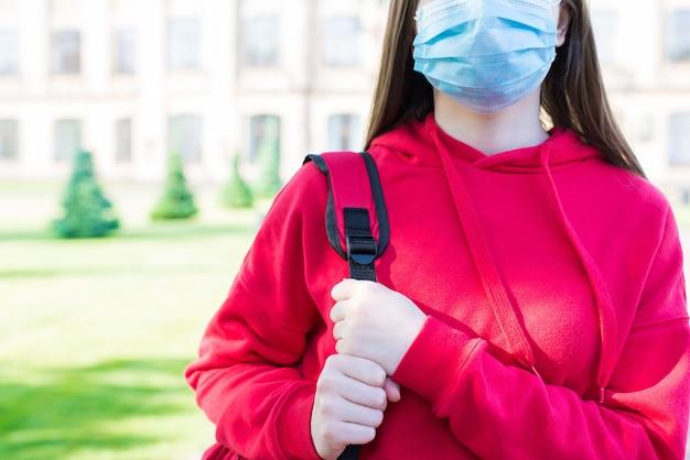 안면 마스크 개념을 사용한 정상적인 생활. 학교 건물 근처에 서 있는 캐주얼한 빨간색 풀오버와 필터 마스크를 쓴 진지한 소녀의 클로즈업 사진 초상화