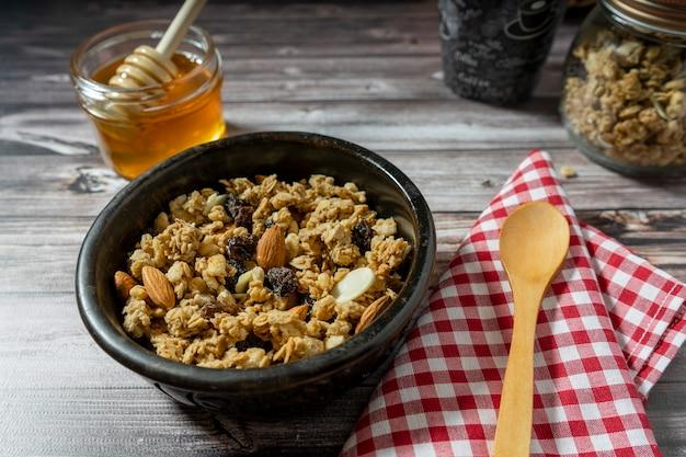 スプーンで木製のテーブルにグラノーラと蜂蜜を添えたボウルの通常のビュー。健康的で自然な食事の概念。