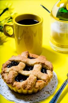 黄色の背景においしいフルーツケーキまたはパスタフローラまたは自家製クロスタッタがあるカフェの通常のビュー。健康的で自然な食事の概念。縦向き。