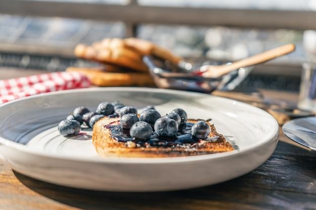 신선한 블루베리와 블루베리 잼을 곁들인 풍부한 빵 토스트의 일반적인 보기. 건강하고 자연스러운 아침 식사 개념입니다.