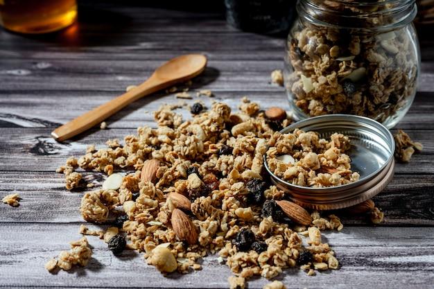 スプーンで木製のテーブルにグラノーラの通常のビュー。健康的で自然な食事の概念。