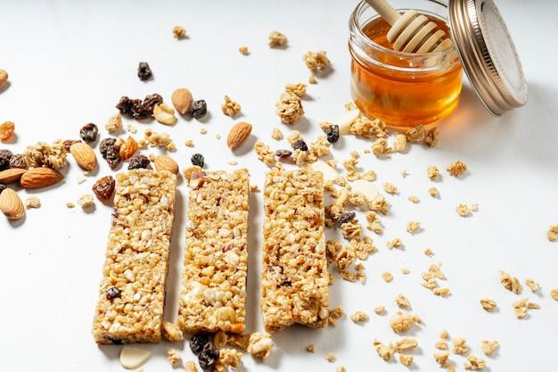 白い表面に天然蜂蜜の瓶とドライフルーツとレーズンのグラノーラまたはシリアルバーの通常のビュー。健康的で自然な食事の概念。
