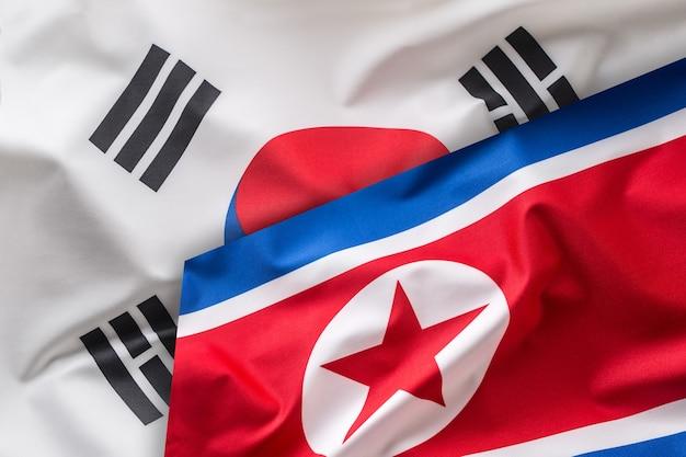 北と南の韓国の旗。カラフルな南と北朝鮮の旗が風に揺れています。