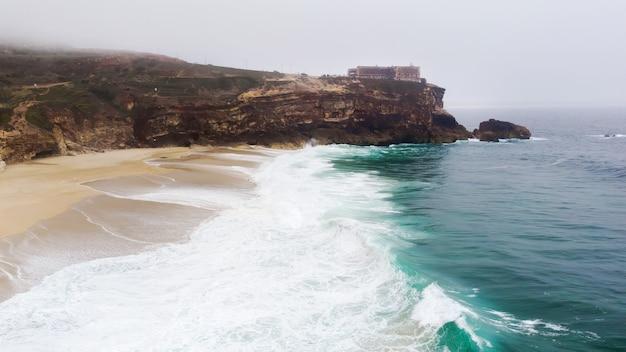 泡立つ波のあるポルトガル、ナザレのノースビーチ