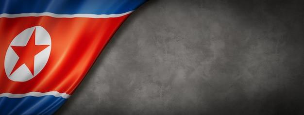 North korea flag on concrete wall. horizontal panoramic banner. 3d illustration