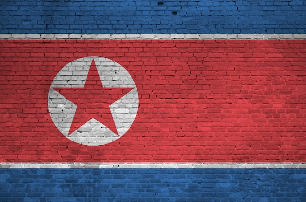 North korea flag depicted in paint colors on old brick wall. textured banner on big brick wall masonry background