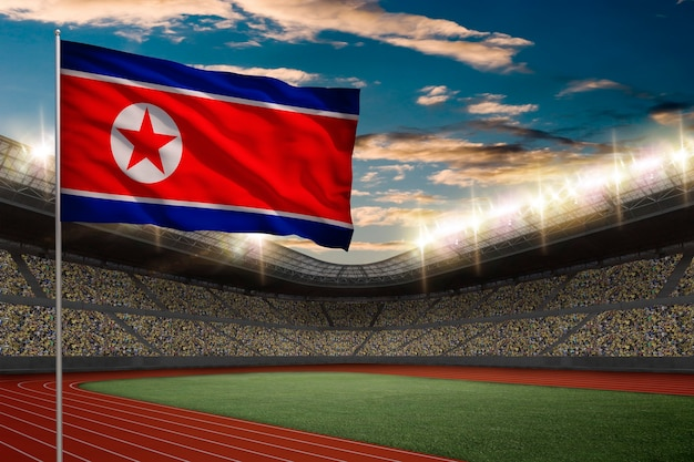 North korea flag in front of a track and field stadium with fans.